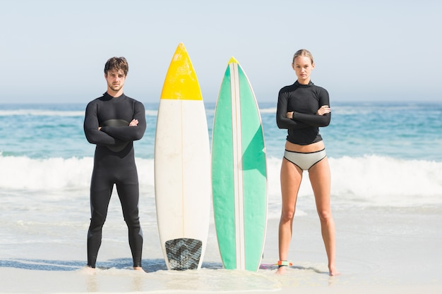 Couple with surfboard standing on the beach