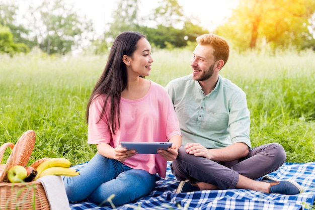 Couple with tablet in park
