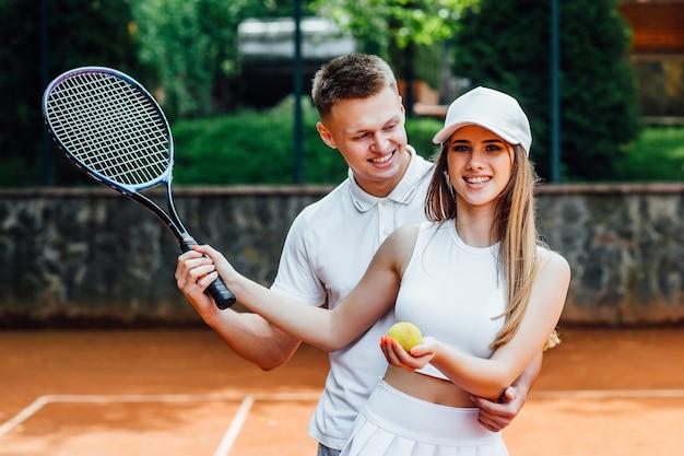 屋外コートでテニスラケットとカップル