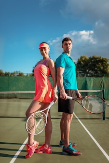 Couple with tennis rackets on outdoor court