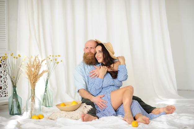 레몬과 흰색 커튼 배경으로 바닥에 앉아 모자를 쓰고 여자와 커플.