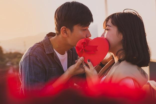 Пара с их ртов покрыты в форме сердца подарочной коробке