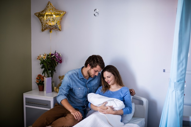 Couple with their newborn baby in the ward