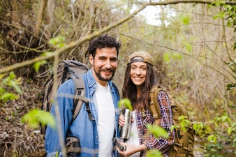 Couple with thermos in forest