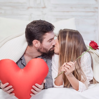 Couple with toy heart kissing on bed