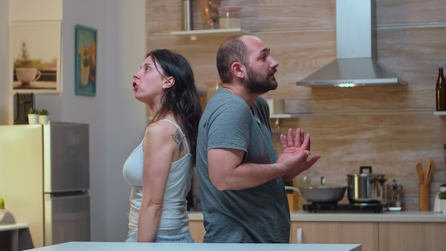 Couple with trust issues fighting back to back. furious, irritated, frustrated, jealous unhappy couple screaming accusing to each other having family conflict disputing sitting in the kitchen.
