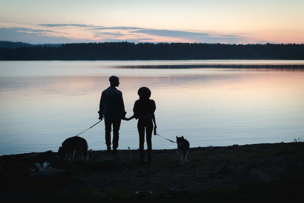 Couple with two dogs on beach