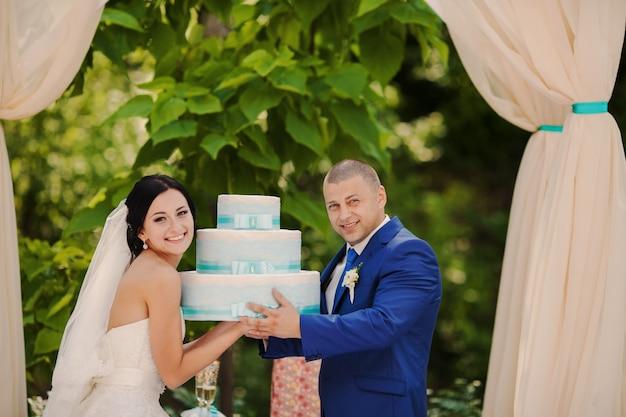 Coppia con torta nuziale nelle loro mani