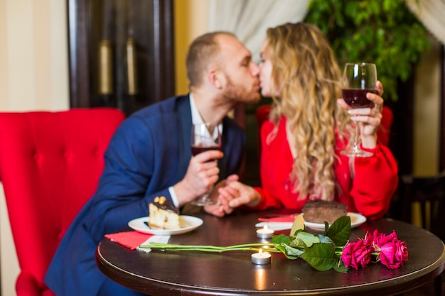 Couple with wine glasses kissing at table