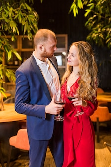 Couple with wine glasses talking in restaurant