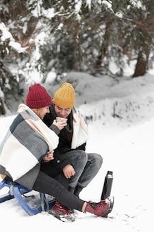 Пара с зимней одеждой сидит на санях и пьет чай