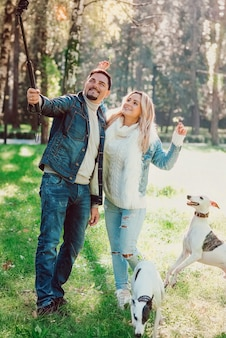 Пара женщина и мужчина в джинсовой одежде гуляют с уиппетами на улице