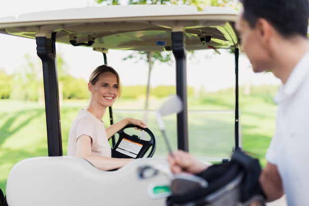 Couple woman is driving golf car on golf course.