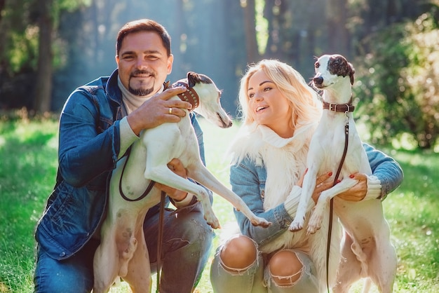 Couple woman and man in denim clothes walking with whippets dogs outdoor