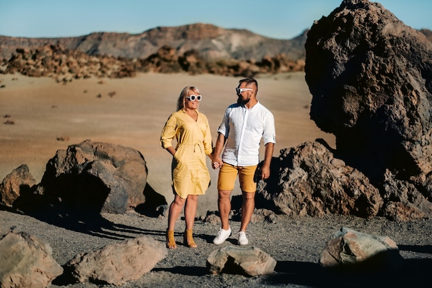A couple, a woman and a man in the desert crater of the teide volcano and enjoy the sunset view. travel to the mountains, freedom and the concept of an active lifestyle.canary islands, spain.