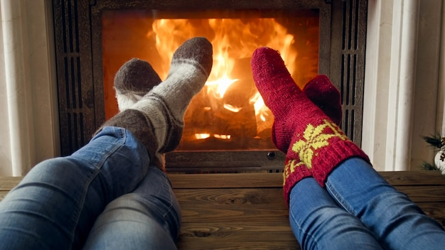 Couple in wool socks relaxing in chalet at burning fireplace