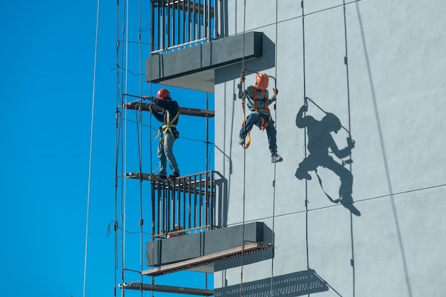 Couple of workers fixing and climbing a scaffolding while following all the safety measures