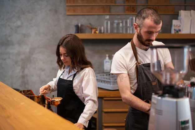 Couple working in coffee shop in aprons