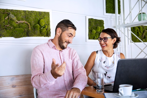 Пара работает из дома, используя ноутбук, пить кофе и говорить о работе. деловая встреча на кухне во время вспышки пандемии коронавируса