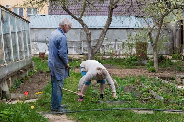 Пара, работающая в саду