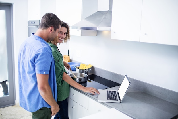 Couple working on laptop while cooking