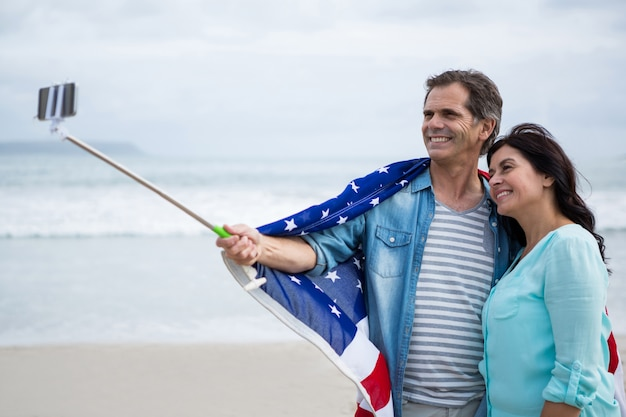 Couple wrapped in american flag taking selfie on beach