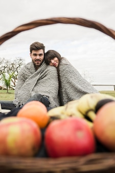 Couple wrapped in one blanket sitting in front of fruits basket