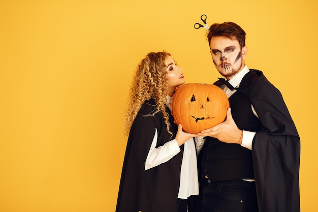 Couple on a yellow background. woman wearing black costume. lady with halloween makeup.