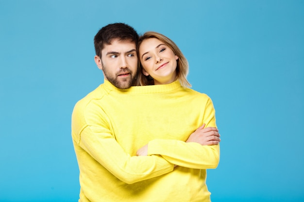 Couple in yellow sweater posing with crossed arms over blue wall