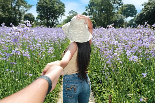 A couple young asian traveler holding hands among naga flower crested field in nature on vacation and having a happy time