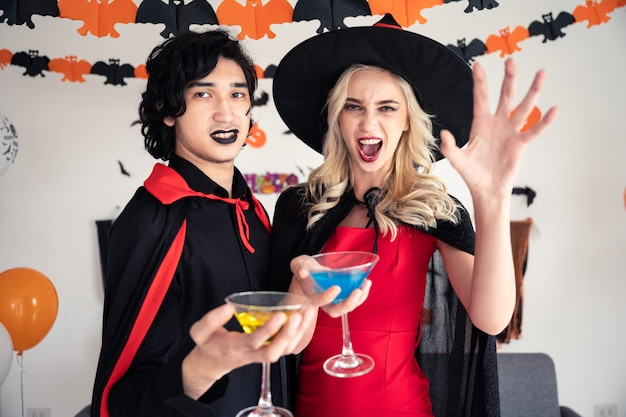 Couple young caucasian man and woman in vampires and witch clothing holding champagne glass