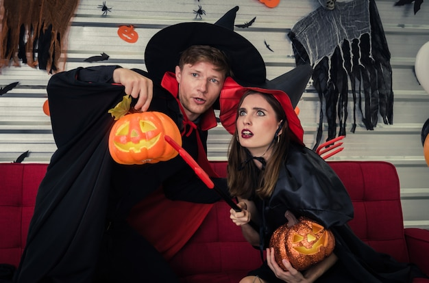 Couple young caucasian in vampire and witch clothing and holding pumpkin