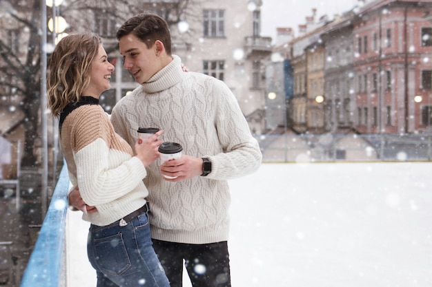 Couple of young couple in love date at the rink it snows drinking cocoa