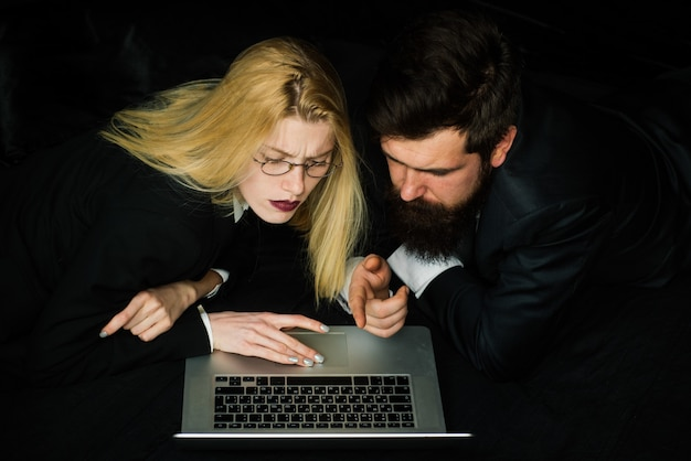 Couple of young coworkers discussing project over a laptop team of businesspeople with computer