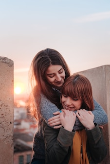 Couple of young girls hugging passionately at sunset