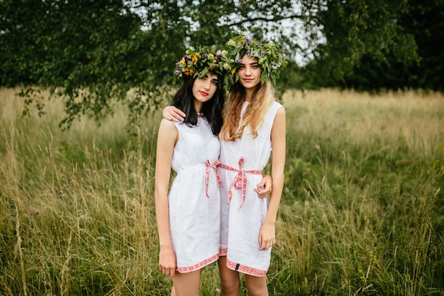 Couple of young girls in love. beautiful slavonic appearance cute females in traditional pagan dresses hugging each other at nature.
