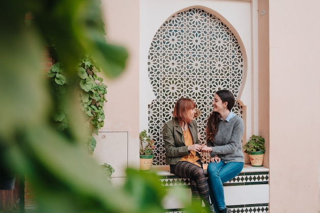 Couple of young girls talking while sitting at an arabic fountain