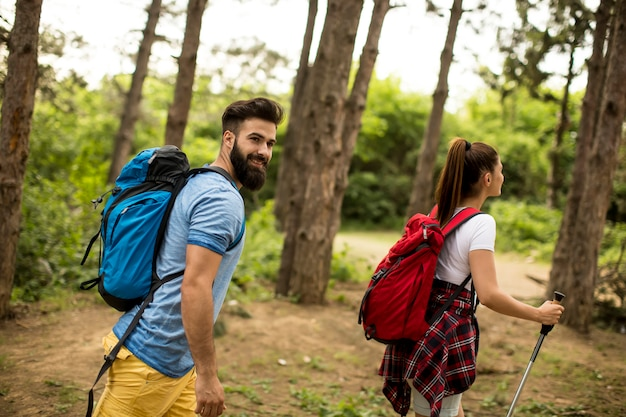 Couple of young happy travelers hiking with backpacks on the beautiful forest trail