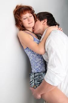 カップルの若い男と白の背景にキスする女性