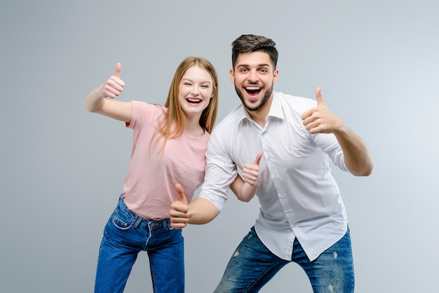 Couple of young man and woman showing thumbs up isolated