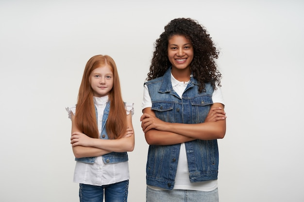 Couple of young pretty curly brunette woman with dark skin and red haired lovely girl wearing family look while posing on white, looking happily and smiling cheerfully