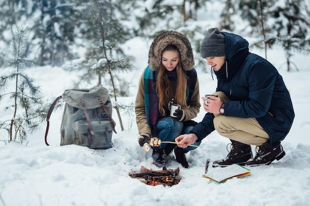 Couple of young travelers roasting marshmallows over bonfire in snowy winter forest