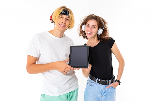 Couple young wife and husband in headphones are holding a tablet  on a white wall