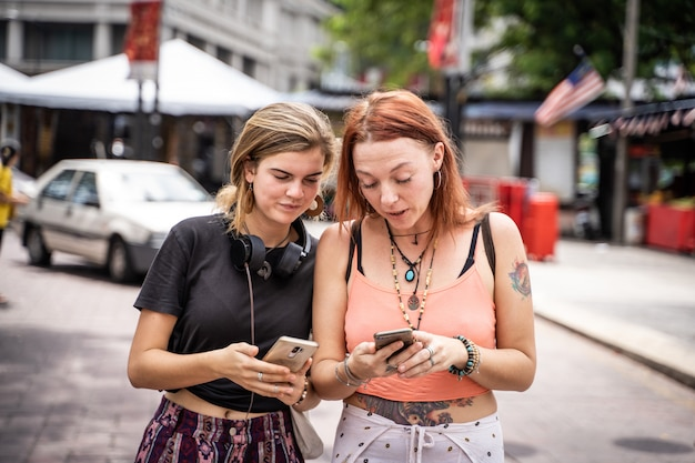 Couple of young women looking at the mobile phone in the street