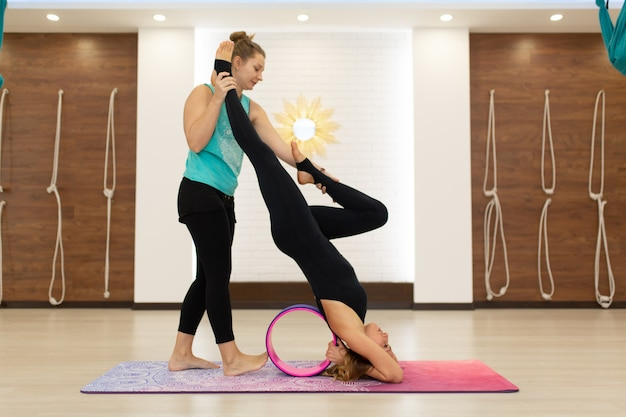 Couple of young women in a sportswear yoga exercises with a yoga wheel in the gym