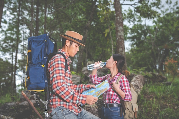 Couples drink water and see a map in the tropical forest along with backpacks in the forest. adventure, traveling, climbing, hike.