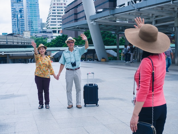 Couples elder and friend travel in city with happy together