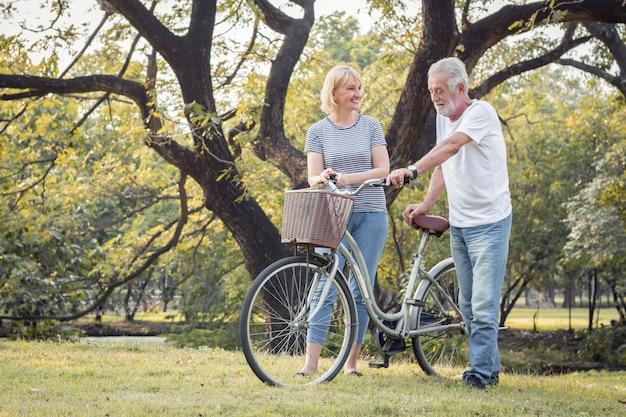 高齢者のカップルは一緒に自転車に乗っています。