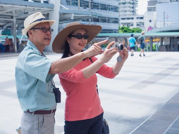 高齢者のカップル旅行都市、高齢者の男性と女性は都市のカメラで何かを撮る