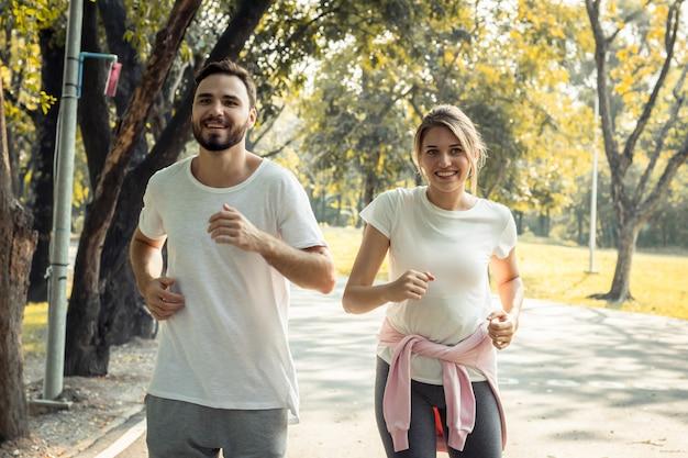 Пары тренируются в парке по утрам.